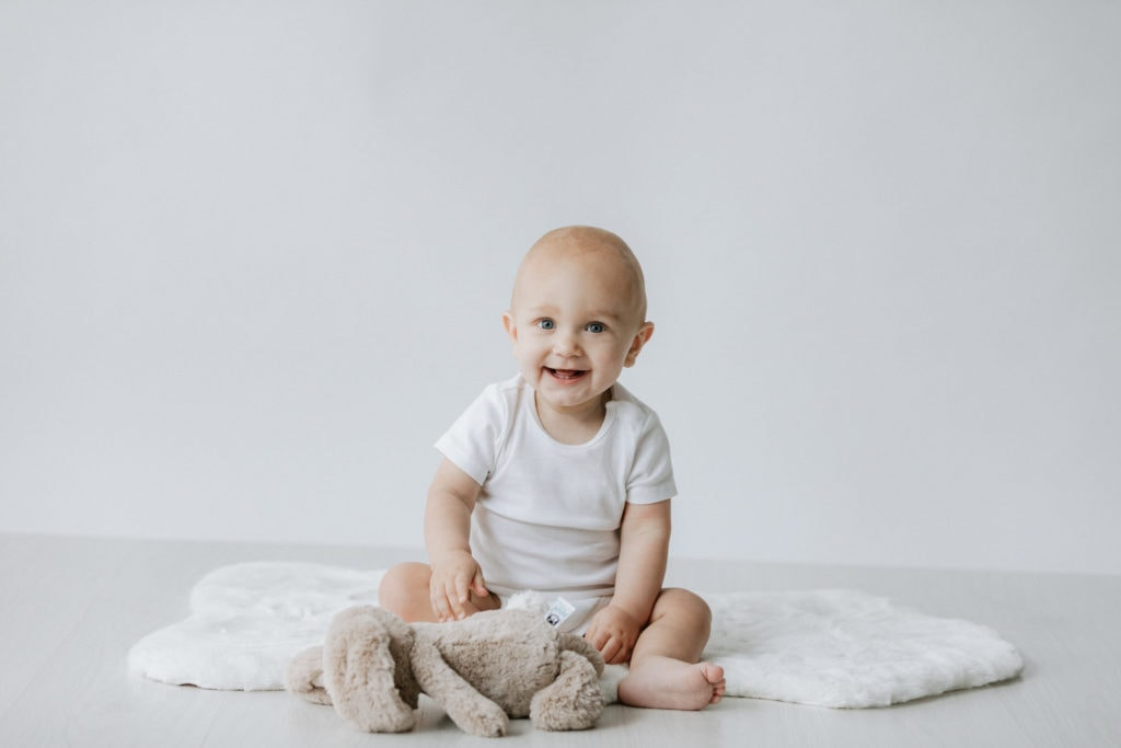 Baby wearing white smiling with a jelly cat teddy taken at his Bexley baby photoshoot