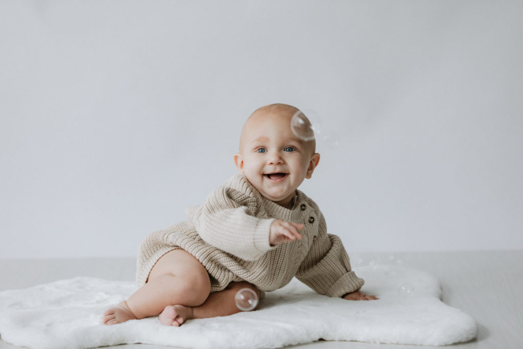 Baby boy wearing knitted romper smiling at his Bexley baby studio photoshoot